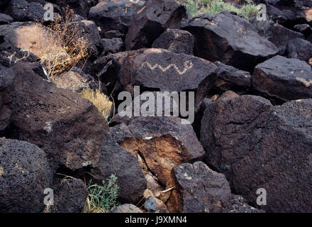 Pueblo carving of a rattlesnake on basalt rocks at Boca Negra Canyon, Petroglyph National Monument, Albuquerque, - Stock Photo