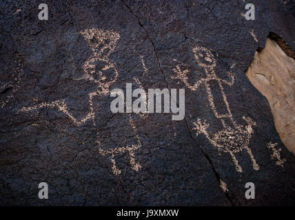 Pueblo ceremonial figures/anthropomorphs carved on basalt rocks at Boca Negra Canyon, Petroglyph National Monument, - Stock Photo