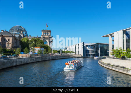 River cruise boat on the Spree River in front of the German parliament buildings, Mitte, Berlin, Germany - Stock Photo