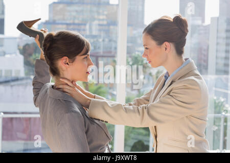Businesswomen having a violent fight in their office - Stock Photo