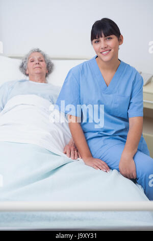 Nurse sitting on a medical bed in hospital ward - Stock Photo