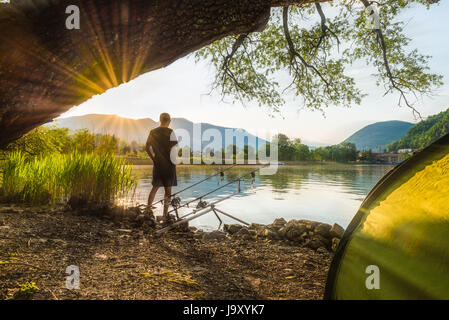 Fishing adventures, carp fishing. Angler, at sunset, is fishing with carpfishing technique. Camping on the shore - Stock Photo