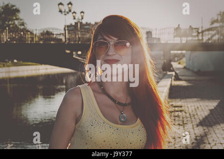 Head and shoulders of ginger hair woman in orange color sunglasses backlit vintage color grading - Stock Photo