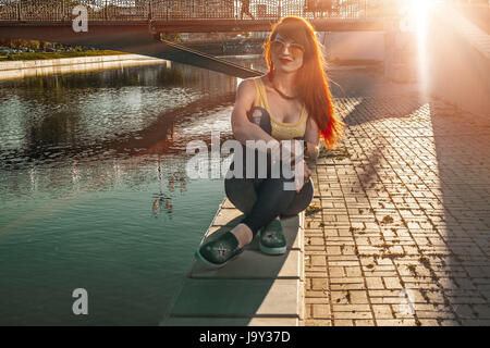 ginger hair woman sitting on city river embankment backlit by sunset - Stock Photo