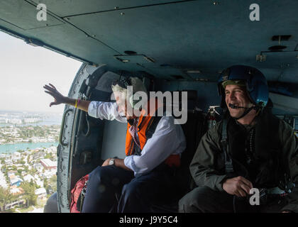 U.S. Florida Congressman Charlie Crist (left) waves out of a U.S. Coast Guard helicopter in flight during an aerial - Stock Photo