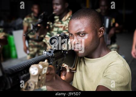 A Cameroonian soldier aims an assault rifle during a close quarter battle drill aboard the USN Spearhead-class expeditionary - Stock Photo