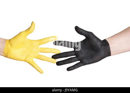 a black and a yellow painted hand in handshake gesture - Stock Photo