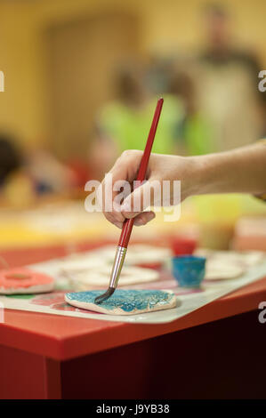 Closeup of hands with art brush, cans with gouache and school classroom art accessories. Pastel color - Stock Photo