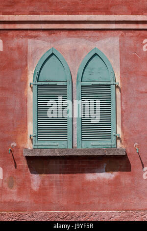 old,slightly weathered green shutters on red brick wall - Stock Photo