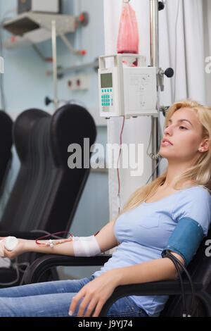 Blonde patient receiving a blood transfusion in hospital ward - Stock Photo