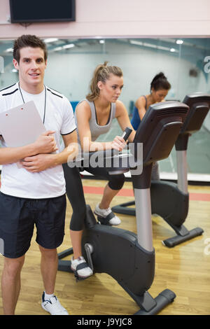Male instructor at spinning class with two women in gym - Stock Photo
