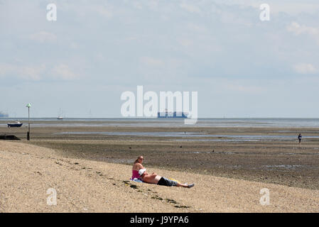 Sunbathers with container ships in the background, in Southend on Sea, Essex, on the Thames Estuary. Beach and foreshore. - Stock Photo