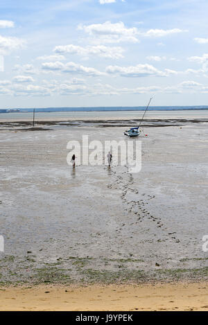 Couple walking back in mud foreshore of Southend on Sea having walked out to a beached yacht. Footprints in mud. - Stock Photo