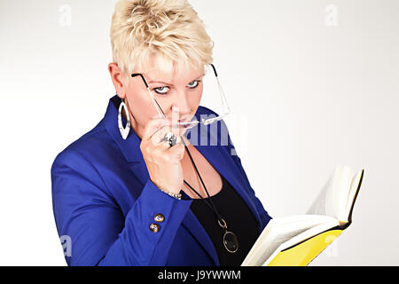 middelaged business woman in jacket with glasses reading a book - Stock Photo