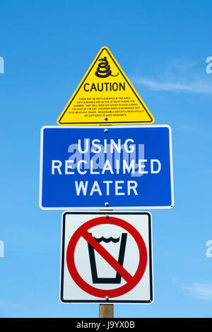 Multiple caution signs at a rest stop in central california. Snake warning yellow triangle, reclaimed water blue - Stock Photo