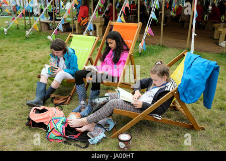 A group of teenagers girls friends reading books sitting on deckchairs on the Hay Festival site Hay-on-Wye, Wales - Stock Photo