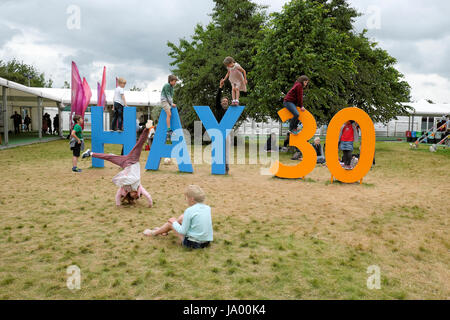Kids playing outside climbing on the Hay 30 sign celebrating the 30th year of the Hay Festival, Hay-on-Wye, Wales - Stock Photo