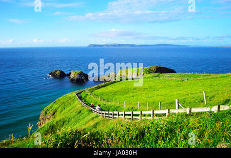 People Walking Along the Coastline Footpath to Carrick-a-Rede Rope Bridge in a Sunny Day, Giant's Causeway, Northern - Stock Photo