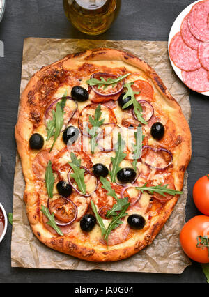 Pizza with tomato, salami and olives on paper over dark background, top view - Stock Photo