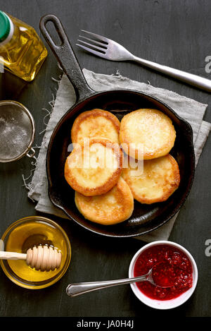 Cheesecakes, curd cheese pancakes in frying pan on dark background, top view - Stock Photo