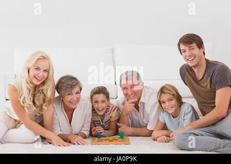 Family looking at the camera with board games in sitting room - Stock Photo