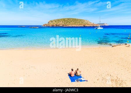 Unidentified young couple of people sunbathing on beautiful sandy Cala Comte beach with azure blue sea water, Ibiza - Stock Photo