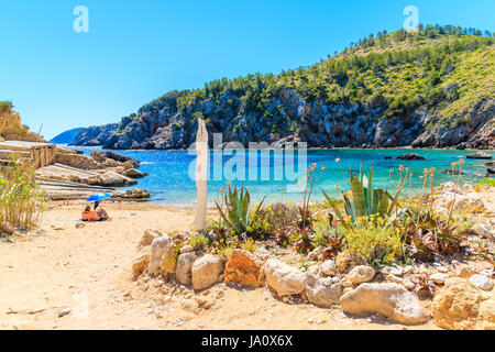 Couple of unidentified people sunbathing on secluded Cala d'en Serra beach, Ibiza island, Spain - Stock Photo
