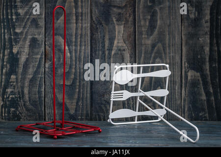 Rolling paper towel standing holder on blue wooden background - Stock Photo