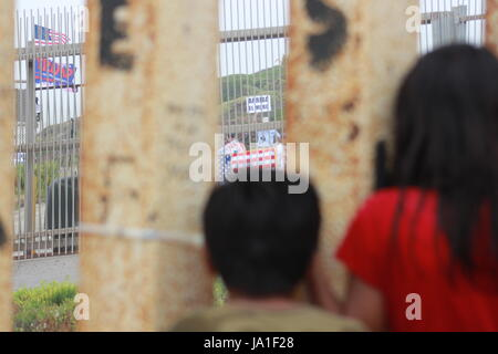 Tijuana, Mexico. 3rd June, 2017. Two Mexican children look at supporters of President Trump waving US-American flags - Stock Photo