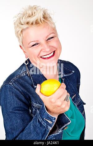 portrait of middelaged beautiful woman eating fresh lemon - Stock Photo