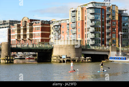 Bristol, England - July 17, 2016: Two women paddleboarding under Redcliffe Bridge on Bristol's Floating Harbour. - Stock Photo