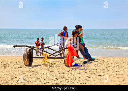 Goa, India - January 27, 2013: Horizontal Beach tropical landscape of paragliding sales assistants sat on a trailer - Stock Photo