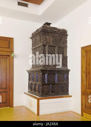 Ornate antique  stove in the corner of a room - Stock Photo