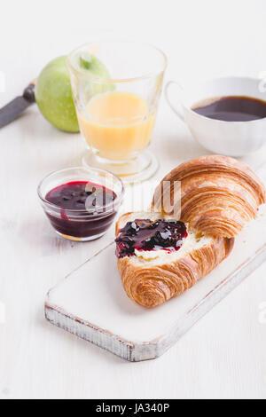 Breakfast on white wooden background - croissant, jam,  orange juice and coffee - Stock Photo