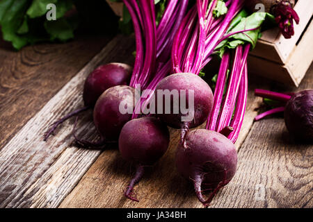 Organic  farm. Fresh beetroot in crate, vegetables on rustic wooden background - Stock Photo