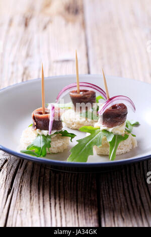 Anchovy canapes garnished with greens and onion - Stock Photo