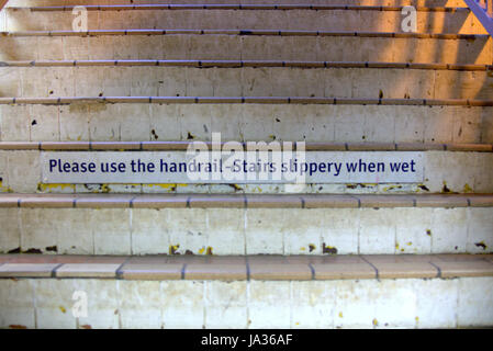please use handrails stairs slippery when wet sign on stairwell - Stock Photo