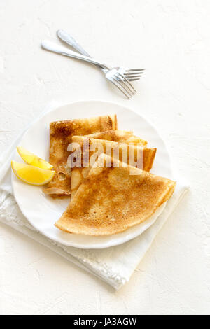 Crepes Suzette with lemon on white plate over white background, copy space. Delicious homemade Crepes for breakfast. - Stock Photo