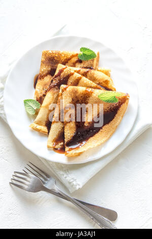 Crepes  with chocolate sauce and mint on white plate over white background, copy space. Delicious homemade Crepes - Stock Photo