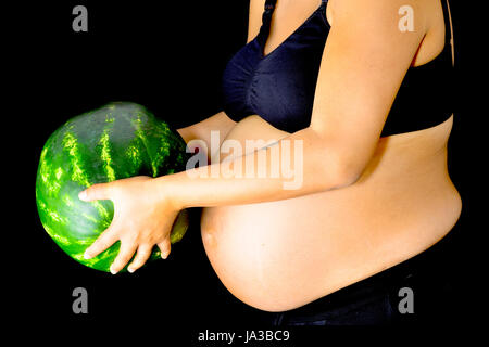 A pregnant woman holding out a huge watermelon in front of her abdomen. - Stock Photo