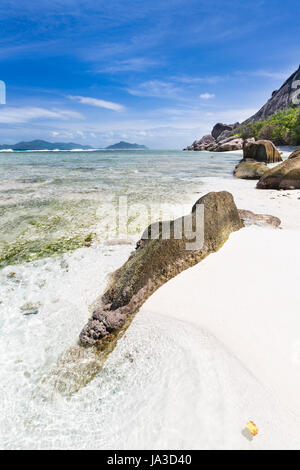 Tropical white beach Anse Pierrot in La Digue, Seychelles with some granite rocks leading into the image and Praslin - Stock Photo