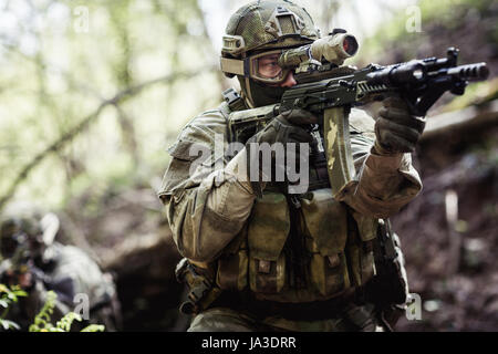 Group of officers on mission in woods during day - Stock Photo