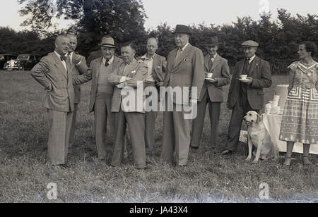 1950s, historical. group of well dressed gentlemen stand together having a cup of tea at a fete or outdoor event. - Stock Photo