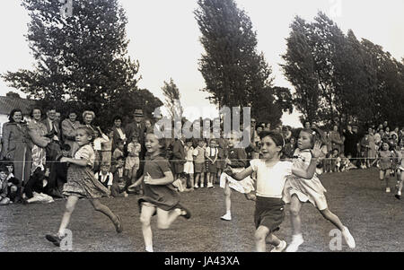 1950s, historical, young girls about to hit the finishing rope in the 60 yard dash at a primary school sports day, - Stock Photo