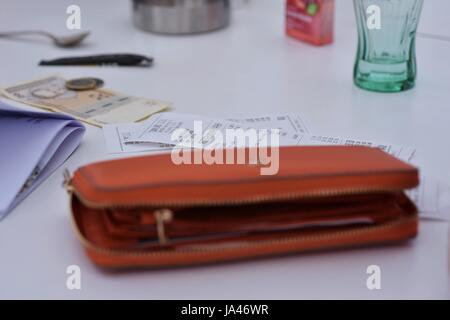 Orange colored ladies wallet on the white table with view of bills and money - Stock Photo