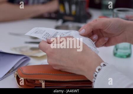 View of woman hands holding bills to pay - Stock Photo