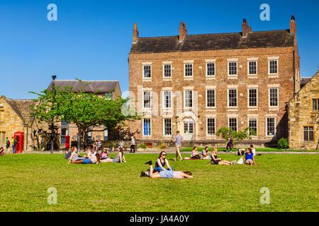 25 May 2017: Durham City, England, UK - students and tourists enjoying the sunshine on Palace Green. - Stock Photo