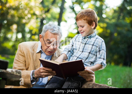 Grandfather and grandson are reading book and learning about nature - Stock Photo