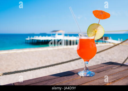 Orange cocktail with apple piece on wooden table. Sunny day near mediterranean sea. Summer time - Stock Photo