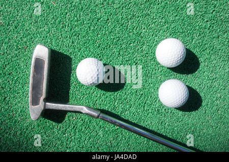 Mini golf scene with ball and club. Can be used like background. Sunny day at resort park - Stock Photo
